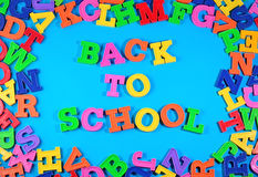 Back to school written by plastic colorful letters on a blue Stock Photography
