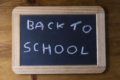 Back to school, written on replica old blackboard writing slate. Royalty Free Stock Images