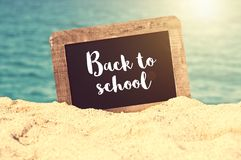 Back to school written on a vintage chalkboard in the sand of a beach Stock Image