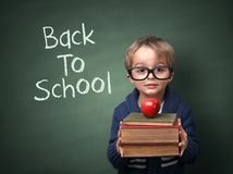 Back to school. Young child holding stack of books and back to school written on chalk blackboard Stock Photos