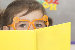 Back to School. Young girl with orange glasses and a yellow book is ready for school Royalty Free Stock Photo