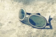 Back to the sky. Sunglasses on the some sort of stone floor Stock Image
