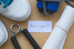 Back to sport. Message written on a piece of paper: Back to sport. Sport items background: snickers,jumping rope,white towel, hand gripper Royalty Free Stock Photo