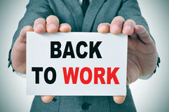Back to work. Businessman holding a signboard with the text back to work written in it Stock Images
