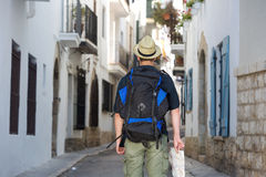 Back of traveling man holding map in town Royalty Free Stock Image
