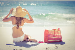 Back turned blonde in swimsuit sitting on the beach Royalty Free Stock Images
