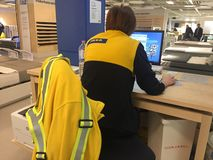 Back turned IKEA workers at desk stock photos