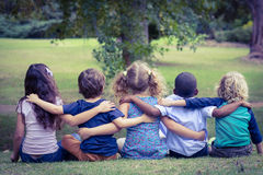 Back turned sitting children in the park Royalty Free Stock Photography