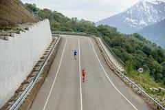 Back two runners running mountain marathon serpentine asphalt road. Rosa Khutor, Russia - May 7, 2017: back two runners running mountain marathon serpentine Royalty Free Stock Photos
