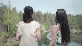 Back of two young woman standing in the top of mountain and looking at amazing view of hill, lake, forest and greens. Girls have black hair and wearing cute stock video footage