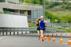Back two young women running in road with traffic cones safety Stock Image