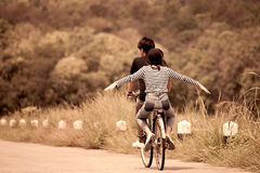 Back veiw of young couple of hipsters riding a bicycle together stock photos