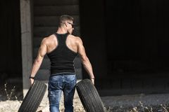 Back of a very trained man. Carry two car tires, wear a high quality workout shirt Stock Photos