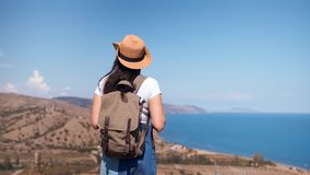 Back view active backpacker woman admiring beautiful seascape approaching top of mountain. Hipster traveler female in hat enjoying nature horizon line clear stock footage