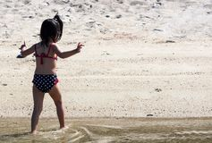 Back view of an adorable cute child toddler in swim suit while walking on water and sand in a beach resort stock photos