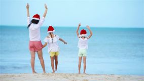 Back view of adorable girl in Christmas hat on white beach during Xmas vacation stock video footage