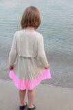 Back view of adorable little girl at white beach during summer vacation Royalty Free Stock Photos