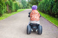 Back view of adorable little girls ride a Royalty Free Stock Image