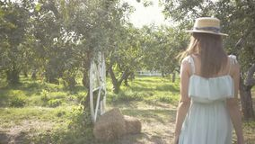 Back view of adorable young woman in straw hat and long white dress walking through the green summer garden. Carefree. Attractive young woman in a straw hat and stock video
