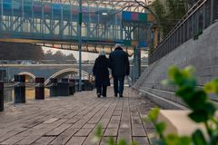 Back view of adult european couple walking near the river on sunset stock photography