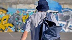 Back view of an adult man with a backpack going towards a graffiti-painted wall. 4K stock video