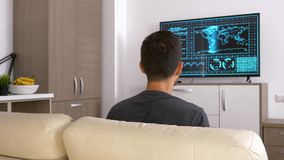 Back view of adult man gaming on the console. On big screen TV in the living room. Dolly slider 4K footage stock footage