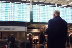 Man near airline schedule. Back view of adult man wearing black coat, holding tickets and passport in hand, checking flight timetable in international airport stock image