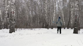 Back view of adult woman is running through the forest stock video