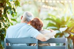 Restful seniors. Back view of affectionate senior spouses having rest on bench in natural environment Stock Images