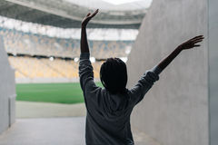 Back view of the afro-american teenager cheering while going to the stadium. Stock Photo