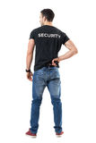 Back view of alerted undercover cop or security agent reaching hand gun attached on belt. Stock Images