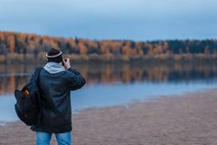 Back view of amateur photographer shooting the autumn scenery of the river. Landscape therapy. Back view of amateur photographer shooting the autumn scenery of stock photos