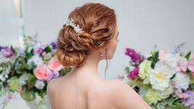 Back view of amazing young bride. Red head woman seat on the chair. Elegant hairstyle. royalty free stock photo