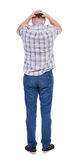 Back view of angry young man in jeans and shirt. Stock Photo