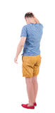 Back view of angry young man in shorts and t-shirt. Royalty Free Stock Images