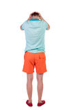Back view of angry young man in shorts and t-shirt. Stock Photos