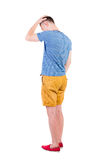 Back view of angry young man in shorts and t-shirt. Royalty Free Stock Image