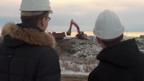 Back view of architects inspecting construction site. Two engineers in hard hats on construction site excavator in the. Background. Engineers examining stock footage