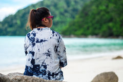 Back view. asia woman wearing sunglasses and indigo shirt sittin Royalty Free Stock Photography