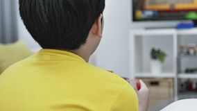 Back view of Asian boy playing video game at home .Slow motion. Back view of Asian boy is playing video game at home .4K Slow motion stock video footage