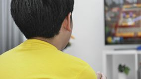 Back view of Asian boy playing video game at home .Slow motion. Back view of Asian boy playing video game at home .4K Slow motion stock video