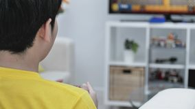 Back view of Asian boy playing video game at home .Slow motion. Back view of Asian boy playing video game at home .4K Slow motion stock footage