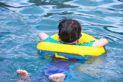 Back view of asian boy with swim tube in pool. Outdoor. Stock Images