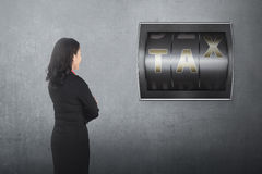 Back view of asian business woman looking counter digit with tax Royalty Free Stock Photos