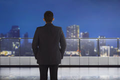 Back view of asian businessman looking at the city through windo Stock Images