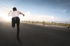 Back view of asian businessman running. On the road Stock Photos