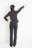 Back view Asian businesswoman pointing away royalty free stock photo