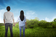 Back view of asian couple holding hand looking at the sky Royalty Free Stock Photography