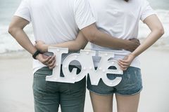 Back view of asian couple holding love sign standing in sea on h royalty free stock photo