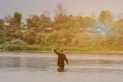 Back view of Asian fisherman throwing fish net to catch fish on stock photo